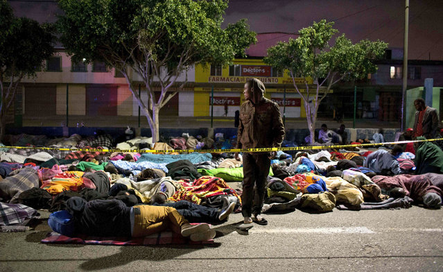 Haitian and African migrants seeking for asylum in the United States, sleep on the street near a Migration office, late on October 2, 2016, in Tijuana, northwestern Mexico. (Photo by Guillermo Arias/AFP Photo)