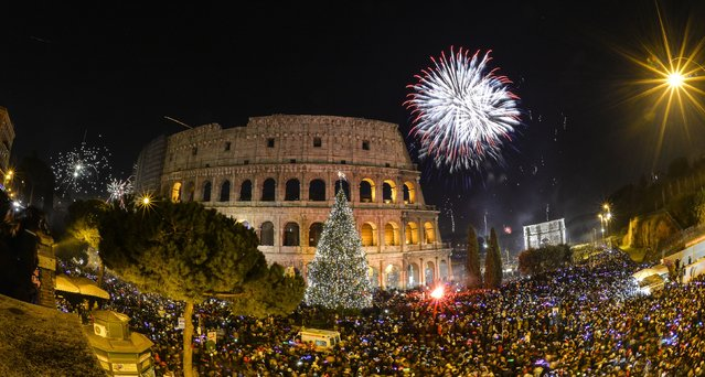 People cheer in front of Rome's ancient Colosseum as fireworks explode to celebrate the new year on January 1, 2015. (Photo by Andreas Solaro/AFP Photo)