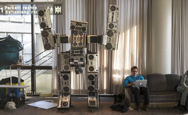 A participants sits with his laptop next to a robot statue built by old ghettoblaster radios at the 31st annual Chaos Communication Congress on December 28, 2014 in Hamburg, Germany. The annual congress is organized by the Chaos Computer Club, Europe's biggest association of computer hackers that has its own code of ethics and in its annual congress seeks to address issues related to society, surveillance, privacy, freedom of information and security. (Photo by Patrick Lux/Getty Images)