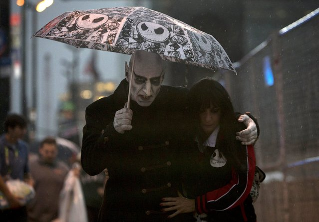 Ken and Lori Caiafa, dressed as Nosferatu and Vampirella, walk through the rain on day two of New York Comic Con in Manhattan, New York, October 9, 2015. (Photo by Andrew Kelly/Reuters)