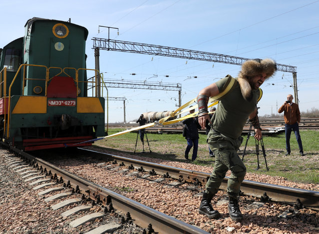 Kazakh strongman Sergei Tsyrulnikov pulls a locomotive with a carriage, weighing about 148 tons in total, during an attempt to set a new country's record for heavyweight pulling in Astana, Kazakhstan May 10, 2018. (Photo by Mukhtar Kholdorbekov/Reuters)