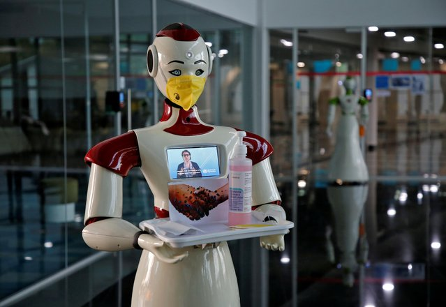 A robot, developed by start-up firm Asimov Robotics, holds a tray with face masks and sanitizer after the two robots were launched to spread awareness about the coronavirus, in Kochi, India, March 17, 2020. (Photo by Sivaram V/Reuters)