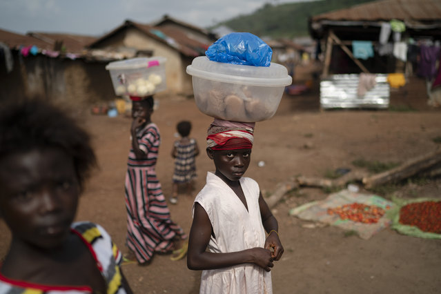 Isatu, 12, carries packets of rice flour to sell at Komao village, on the outskirts of Koidu, district of Kono, Sierra Leone, Sunday, November 22, 2020. Sierra Leone closed its borders before the country had its first COVID-19 case. As a result, the country has seen only 2,434 confirmed cases and 74 deaths. Only 76 of those cases were confirmed in Kono district, but the economic toll here has brought many families already living on the edge to a breaking point.(Photo by Leo Correa/AP Photo)