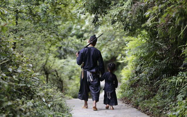 Ethnic Miao man Gun Yuangu, 45, walks with his grandson in the village of Basha in Congjiang county, Guizhou province, May 28, 2013. The village, an old ethnic Miao settlement with a population of 2,200, is believed to be the last community authorized by the Chinese government to keep guns. Although people in Basha no longer subsist on hunting, guns and gunpowder pots have become part of their traditional dress, while firing towards the sky is seen as a ritual to welcome guests, according to local media. (Photo by Jason Lee/Reuters)