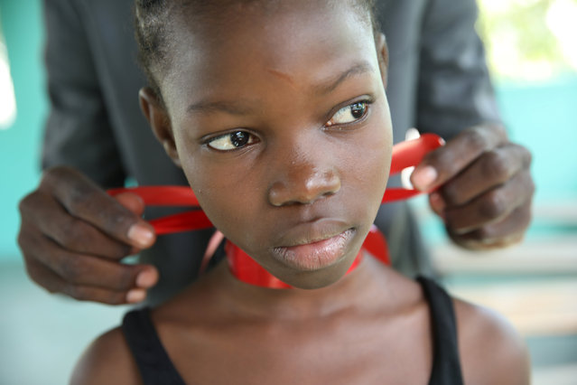 A girl prepares before performing a dance in front of Spain's Queen Letizia at the Center of the Sisters of Saint Vincent de Paul in Cite Soleil, Port-au-Prince, Haiti, May 23, 2018. (Photo by Andres Martinez Casares/Reuters)