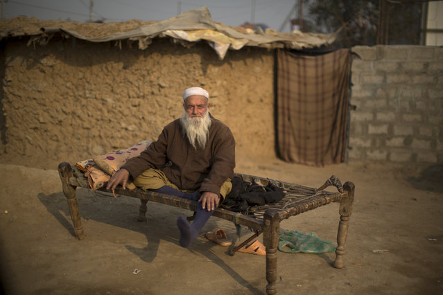 An elderly Pakistani man, who was displaced with his family from Pakistan's tribal region of Mohmand Agency due to fighting between the Taliban and the army, sits on a bed in front of his mud house on the outskirts of Islamabad, Pakistan, Monday, Dec. 29, 2014. (AP Photo/Muhammed Muheisen)