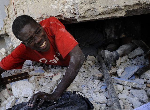 Mac Fanieh tries to rescue a live teacher trapped amid the rubble of the earthquake as he crawls past a schoolgirl that died at Ecole St. Gerard on January 14, 2010 in Port-au-Prince, Haiti. (Photo by Carol Guzy/The Washington Post via Getty Images )