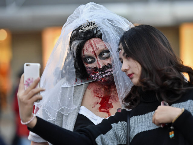 Women dressed in Halloween costumes pose for a selfie before participating in the zombie walk in Essen, Germany, Monday, October 31, 2016. Many hundreds of young disguised zombies celebrate Halloween at Germany's biggest horror walk through the city center of Essen. (Photo by Martin Meissner/AP Photo)