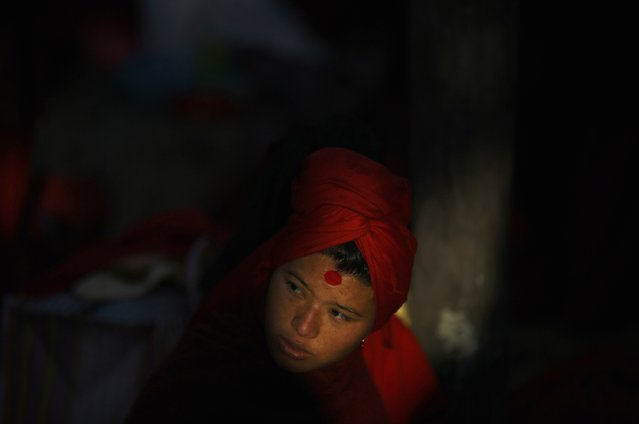 Light illuminates a devotee as she sits in the sun after taking a holy bath during the Swasthani Bratakatha festival in the Triveni River in Panauti near Kathmandu January 24, 2015. (Photo by Navesh Chitrakar/Reuters)