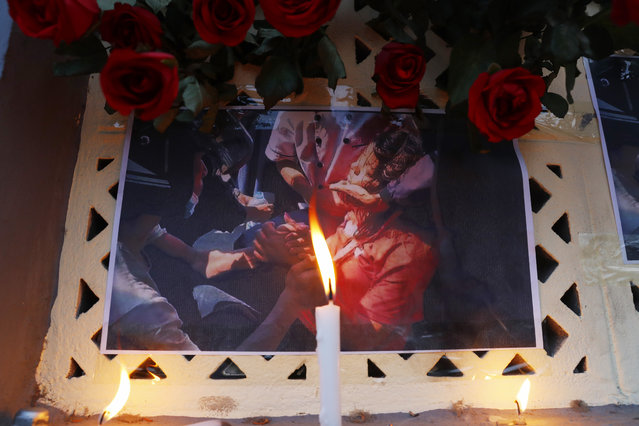 A candle is lit in front of a photo of Mya Thwet Thwet Khine in Mandalay, Myanmar Friday, February 19, 2021. Mya Thwet Thwet Khine, the young woman who was shot in the head by police during a protest last week against the military's takeover of power in Myanmar died Friday morning, her family said. (Photo by AP Photo/Stringer)