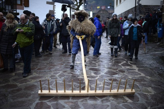 A man walks with a giant rake during carnival celebrations in Zubieta January 27, 2015. Bell carrying dancers known as Joaldunak from Zubieta and neighbouring Ituren visit each other's villages performing a ritual dance to ward off evil spirits and awaken the coming spring. Alongside the dancers, villagers dress in bizarre and frightening costumes to harass and scare visitors. (Photo by Vincent West/Reuters)