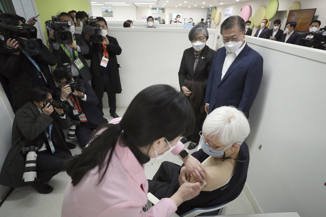 South Korean President Moon Jae-in, top right, watches a doctor receives a shot of AstraZeneca vaccine at a public health center in Seoul, South Korea, Friday, February 26, 2021. South Korea on Friday administered its first available shots of coronavirus vaccines to people at long-term care facilities, launching a mass immunization campaign that health authorities hope will restore some level of normalcy by the end of the year. (Photo by Choe Jae-koo/Yonhap via AP Photo)