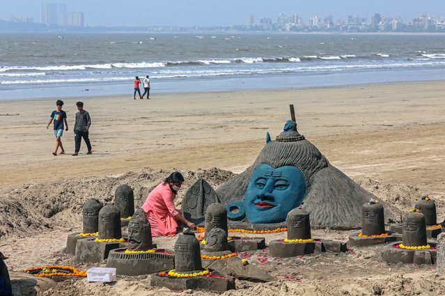 Devotees perform rituals to a sand sculpture of Hindu god Lord Shiva, made by Indian sand artist Laxmi Gaud for visitors and tourists to see on the occasion of Maha Shivaratri at the Juhu beach in Mumbai, India, 11 March 2021. The Maha Shivaratri festival is celebrated by Hindus in honor of Lord Shiva with ritual bathing of Shivalingams and prayers. According to one of the most popular legends Shivaratri is the wedding day of Lord Shiva and Parvati. (Photo by Divyakant Solanki/EPA/EFE)