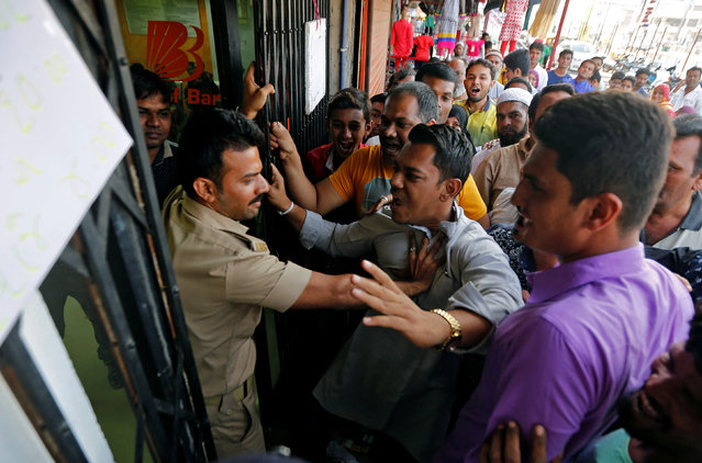 People scuffle with a policeman as they try to enter a bank to exchange their old high denomination banknotes in Ahmedabad, India, November 17, 2016. (Photo by Amit Dave/Reuters)