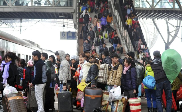Passengers carry their luggage as they queue to board a train at a railway station in Nanjing, Jiangsu province February 2, 2015. Chinese Ministry of Transport said a total of 2.807 billion trips are expected to be made during the 40-day Spring Festival travel rush, which will begin on February 4 and last until March 16, Xinhua News Agency reported. (Photo by Reuters/Stringer)