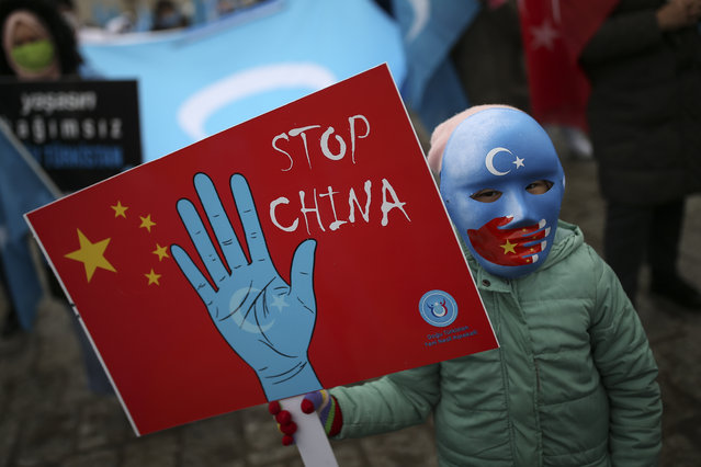A protester from the Uyghur community living in Turkey, holds an anti-China placard during a protest in Istanbul, Thursday, March 25, against against the visit of China's FM Wang Yi to Turkey. (Photo by Emrah Gurel/AP Photo)