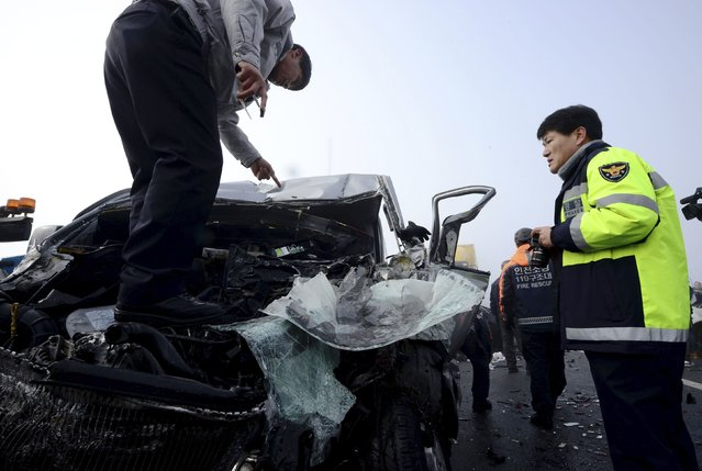 Policemen examine a damaged vehicle on Yeongjong Bridge in Incheon February 11, 2015. (Photo by Park Jung-ho/Reuters/News1)