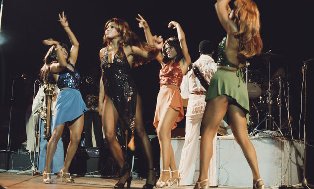 American singer Tina Turner performing live on stage with Ike Turner (behind) and the Ikettes in London, 28th October 1975. (Photo by Michael Putland/Getty Images)