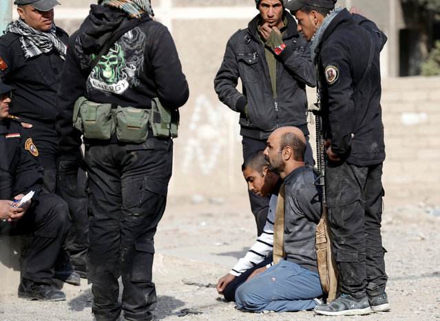 Members of an Iraqi Special forces intelligence team talk to suspected Islamic State fighters in Mosul, Iraq November 27, 2016. (Photo by Goran Tomasevic/Reuters)