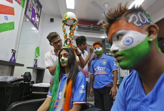 A hairdresser attaches a replica of the Cricket World Cup trophy, which consists of silicone hair, on the head of cricket fan at a saloon during a promotional event in Mumbai February 12, 2015. (Photo by Shailesh Andrade/Reuters)