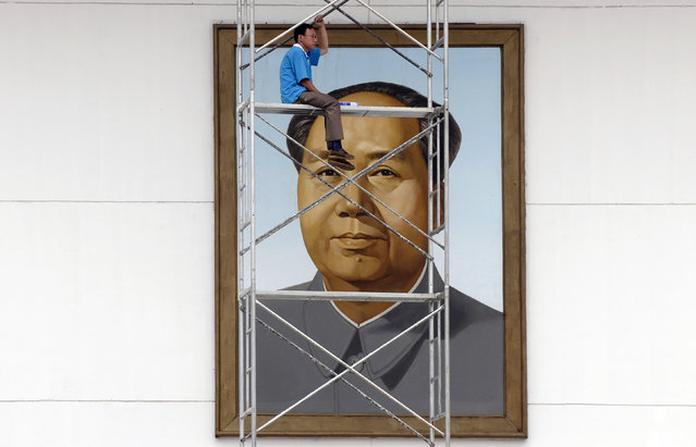 A laborer rests on scaffolding in front of a portrait of late Chairman Mao Zedong at the city square in Changzhi, Shanxi province, July 10, 2009. (Photo by Reuters/Stringer)