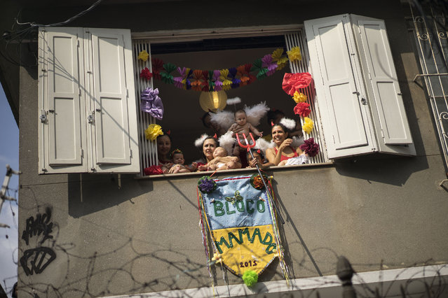 """People and babies wearing carnival costumes watch the """"Ceu na Terra"""", or Heaven on earth, carnival parade in Rio de Janeiro, Brazil, Saturday, February 14, 2015. (Photo by Felipe Dana/AP Photo)"""