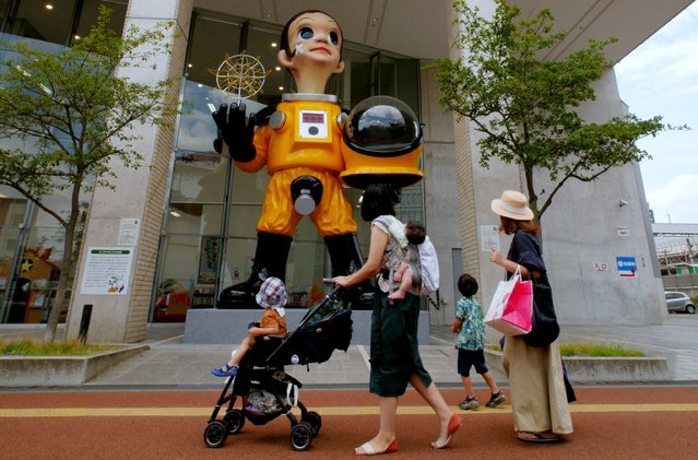 Women and children look at a statue of a child wearing what appears to be a hazardous material suit in Fukushima, Japan on August 15, 2018. (Photo by Kwiyeon Ha/Reuters)
