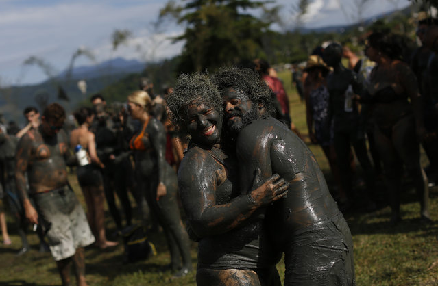 "A mud covered couple dance during the traditional ""Bloco da Lama"" or ""Mud Block"" carnival party, in Paraty, Brazil, Saturday, February 14, 2015. Legend has it the ""bloco"" was born in 1986 after local teens hiking in a nearby mangrove forest smeared themselves with mud to discourage mosquitoes and then wandered through Paraty. (Photo by Leo Correa/AP Photo)"