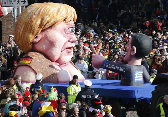 A carnival float depicting German Chancelor Angela Merkel  as a mythical Cyclops and Greek premier Alexis Tsipras attacking her  during the traditional Rose Monday carnival parade in Duesseldorf, Germany, Monday, February 16, 2015. (Photo by Frank Augstein/AP Photo)