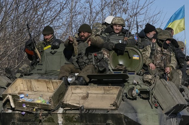 Ukrainian servicemen ride on a military vehicle as they leave an area around Debaltseve, eastern Ukraine near Artemivsk, February 18, 2015. (Photo by Gleb Garanich/Reuters)