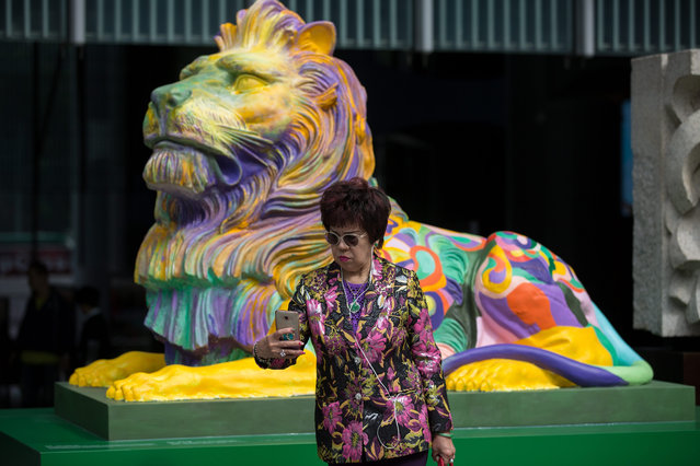 "A woman takes a selfie next to a replica of the HSBC lion painted in rainbow colours and displayed outside the bank's headquarters in Hong Kong, China, 06 December 2016. Several groups of activist including The Family School SODO Concern Group, Parents for the Family Association, Overturning LGBT Agenda and Next Generation Orientation have launched a joint online signature campaign expressing disapproval at the display. The groups claimed the rainbow lions have offended both HSBC customers and shareholders. The bank kicked off the ""Celebrate Pride, Celebrate Unity"" campaign in November by displaying replicas of the bank's iconic lions in rainbow colours, created by a local LGBT artist, in front of its Hong Kong headquarters. (Photo by  Jerome Favre/EPA)"