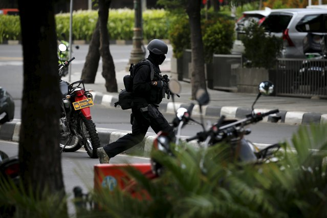 An armed Indonesian police runs across a street at Thamrin business district in Jakarta  January 14, 2016. Five militants, including one foreigner, were killed in the gun and bomb assault in central Jakarta, Indonesia's chief security minister said on Thursday. (Photo by Reuters/Beawiharta)