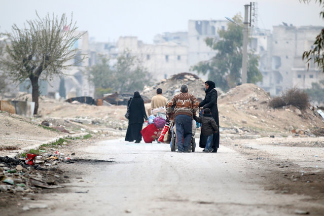 People carry their belongings as they flee the Kadi Askar area towards Bustan al-Qasr neighbourhood, in rebel-held besieged Kadi Askar area of Aleppo, Syria December 5, 2016. (Photo by Abdalrhman Ismail/Reuters)