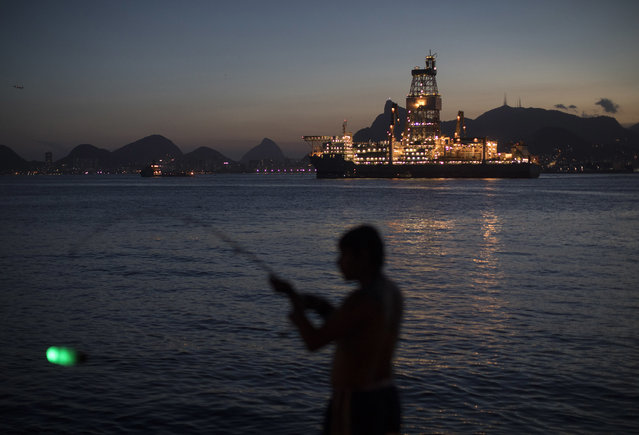 In this March 28, 2018 photo, a man holds his fishing rod carrying an illuminated bobber, on the shore of Guanabara Bay where Petrobras operates its ultra-deep drilling vessel Laguna Star NS-44 in Niteroi, Brazil. Brazil's Petrobras says profit rose 56 percent in first quarter of the year as the state-controlled oil company is beginning to emerge from a massive corruption scandal. (Photo by Leo Correa/AP Photo)