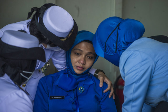 Military personnel console a sailor's wife during a remembrance ceremony for the crew of the Indonesian navy submarine KRI Nanggala that sank on April 21 during a training exercise, on the deck of the hospital ship KRI Dr. Soeharso off the coast of Bali on April 30, 2021. (Photo by Juni Kriswanto/AFP Photo)