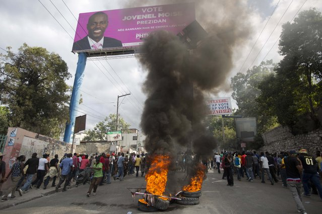 Demonstrators burn tires under campaign poster of presidential candidate Jovenel Moise of the PHTK political party during a street protest after it was announced that the runoff Jan. 24, presidential election had been postponed, in Port-au-Prince, Haiti, Friday, January 22, 2016. (Photo by Dieu Nalio Chery/AP Photo)