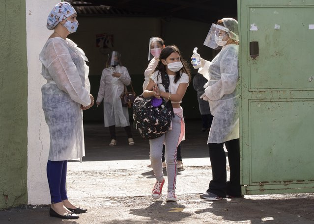 Students exit a public school in Serrana, Sao Paulo state, Brazil, Friday, May 28, 2021. Brazil's Butantan Institute has finished a mass vaccination of the city's entire adult population with doses of Sinovac, to test the new coronavirus' behavior in response to the vaccine. (Photo by Andre Penner/AP Photo)