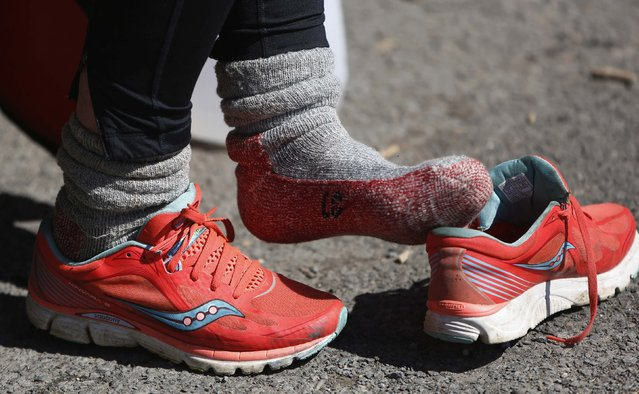 Sixty-eight year old cross-country runner Rosie Swale-Pope puts on her socks and running shoes in Upperville, Virginia March 13, 2015. (Photo by Gary Cameron/Reuters)