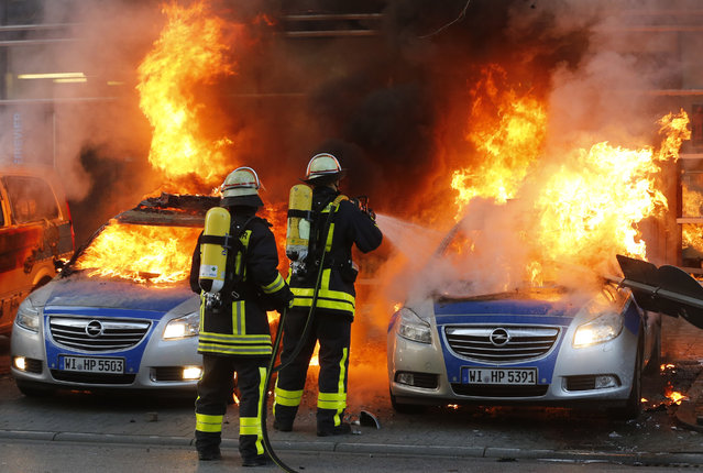 Firefighters extinguish flames in burning police cars that were set afire Wednesday, March 18, 2015 in Frankfurt, Germany. (Photo by Michael Probst/AP Photo)