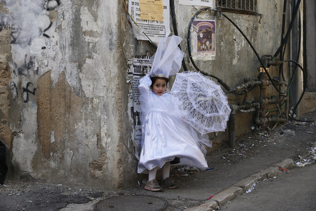 An ultra-Orthodox Jewish girl dressed as a bride stands on a sidewalk during celebrations marking the Jewish holiday of Purim in Jerusalem's Mea Shearim neighbourhood March 6, 2015. Purim is a celebration of the Jews' salvation from genocide in ancient Persia, as recounted in the Book of Esther. (Photo by Ammar Awad/Reuters)
