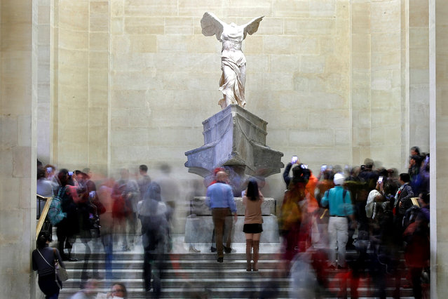Visitors look at the Winged Victory of Samothrace, also called the Nike of Samothrace, a marble Hellenistic sculpture at the Louvre Museum in Paris, France, December 3, 2018. (Photo by Charles Platiau/Reuters)