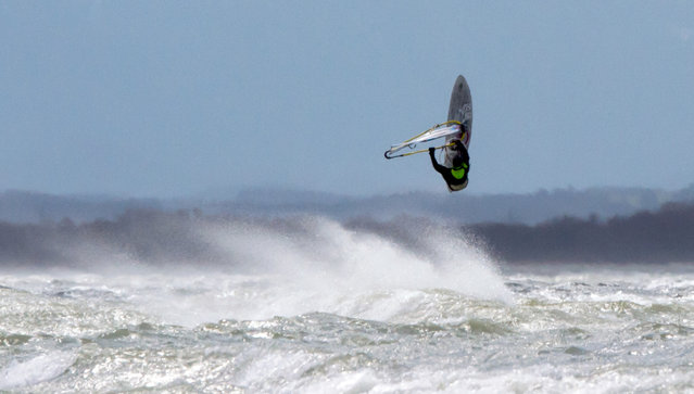 A surfer enjoys the heavy wind on lake Ammersee near Herrsching, southern Germany, Tuesday, March 31, 2015. (Photo by Peter Kneffel/AP Photo/DPA)