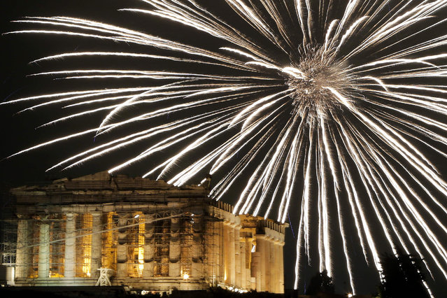 Fireworks explode above the ancient Parthenon temple atop the Acropolis hill during New Year celebrations in Athens on January 1, 2017. (Photo by Angelos Tzortzinis/AFP Photo)