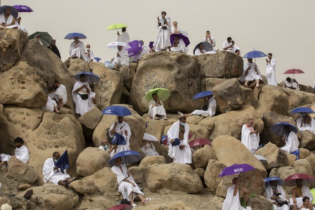 Muslim pilgrims pray on top of the rocky hill known as the Mountain of Mercy, on the Plain of Arafat, beside inscriptions which were left by pilgrims from previous years, during the annual hajj pilgrimage, near the holy city of Mecca, Saudi Arabia, Monday, July 19, 2021. The coronavirus has taken its toll on the hajj for a second year running. What once drew some 2.5 million Muslims from all walks of life from across the globe, the hajj pilgrimage is now almost unrecognizable in scale. (Photo by Amr Nabil/AP Photo)