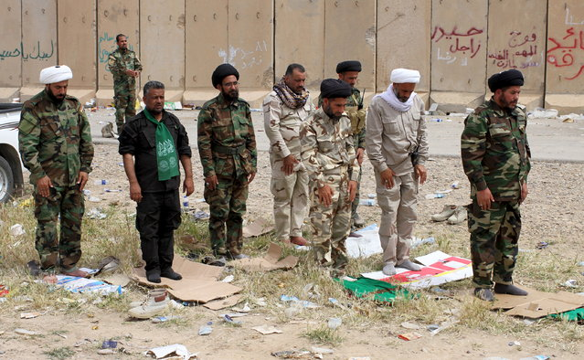 Shiite clerics from Hashid Shaabi (Popular Mobilization) forces, allied with Iraqi forces against the Islamic State, pray in Tikrit, March 28, 2015. (Photo by Thaier Al-Sudani/Reuters)