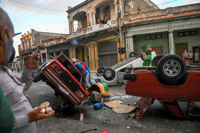 """Police cars are seen overturned in the street in the framework of a demonstration against Cuban President Miguel Diaz-Canel in Havana, on July 11, 2021. Thousands of Cubans took part in rare protests Sunday against the communist government, marching through a town chanting """"Down with the dictatorship"""" and """"We want liberty"""". (Photo by Yamil Lage/AFP Photo)"""