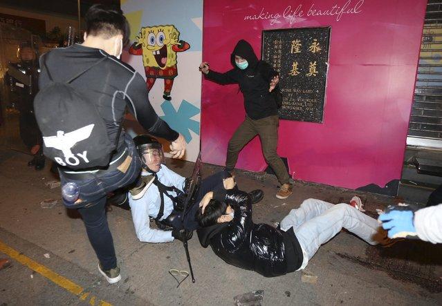 A protester (L) kicks a policeman (2nd L) who has fallen down during a clash at Mongkok district in Hong Kong, China February 9, 2016. (Photo by Fu Chun-wai/Reuters/E Weekly)