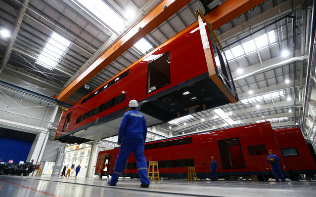 "Employees work on an electric train assembly line at the ""Stadler Minsk"" plant in Fanipol, Belarus February 10, 2016. (Photo by Vasily Fedosenko/Reuters)"