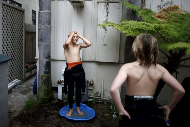 Kevin Elliott, 12, (L) uses the outdoor shower in their friend Kieran Walls' (not shown) yard as Shane Moseley, 13, waits for his turn after surfing at sunrise in Hermosa Beach, California March 31, 2015. (Photo by Lucy Nicholson/Reuters)