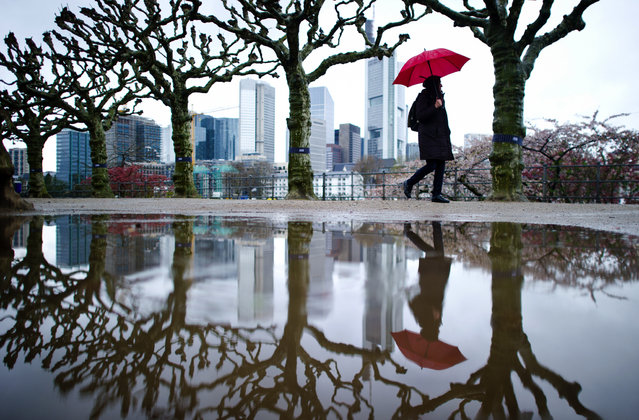 A woman is reflected in a puddle as she walks alongside the bank of the river Main in Frankfurt, Germany, Thursday, April 2, 2015. (Photo by Christoph Schmidt/AP Photo/DPA)